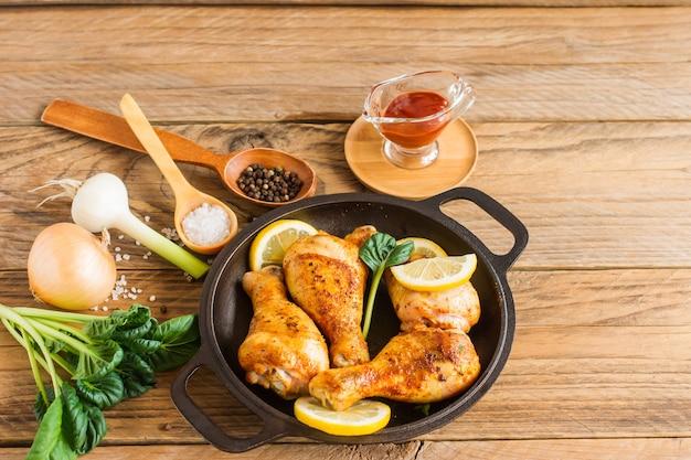Geroosterde kippenpoten in pan met groentesalade en ketchup
