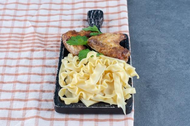 Geroosterde kippenvleugels en macaroni op zwart bord.