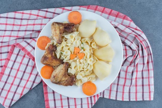 Geroosterde kippenvleugels en pasta op witte plaat.