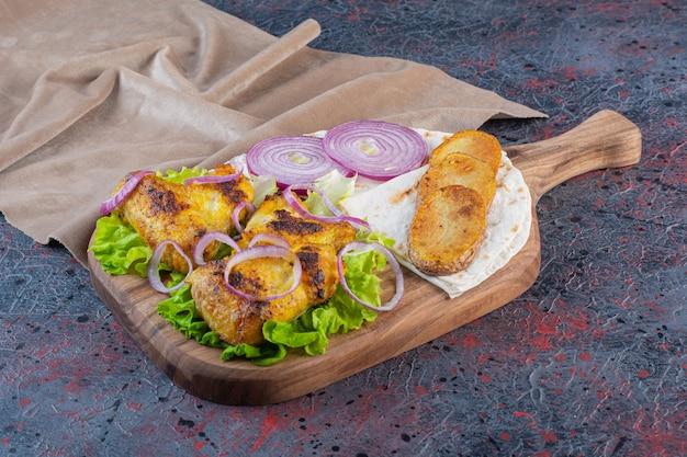 Geroosterde kippenvleugels met groenten op houten snijplank.