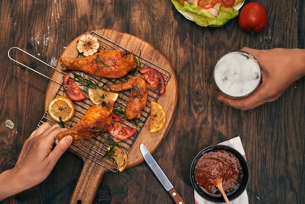 Geroosterde kippenvleugels op bakplaat over houten tafel met kopieerruimte. bovenaanzicht, plat gelegd