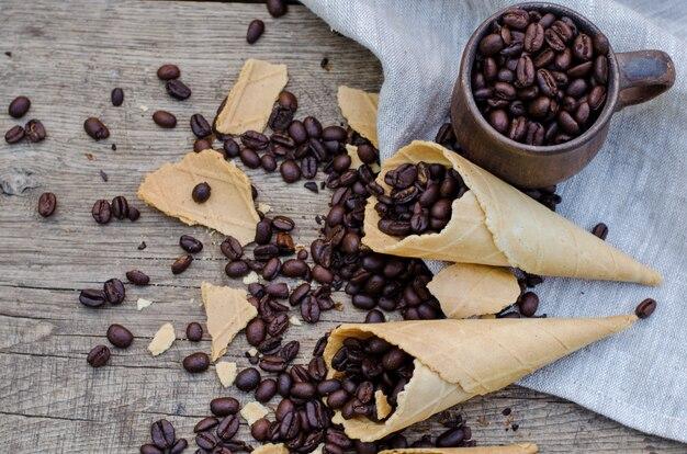 Geroosterde koffiebonen in een ceramische mok en suikerwafelkegels op houten