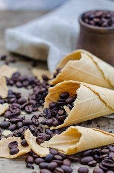 Geroosterde koffiebonen in een keramische mok en suikerwafelkegels