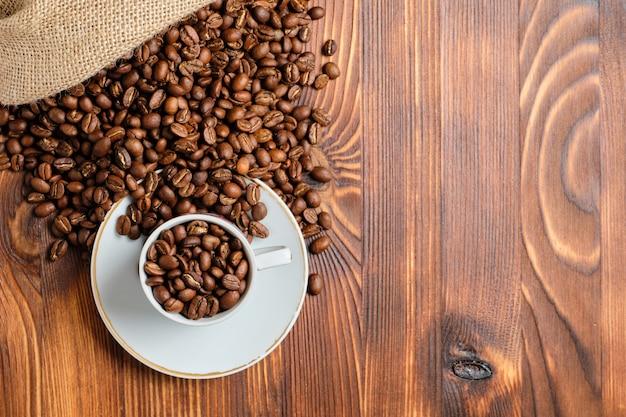 Geroosterde koffiebonen in een witte kop en een gebreide zak op een gebrande houten achtergrond.