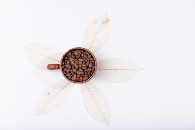 Geroosterde koffiebonen in houten kop over gedroogd blad