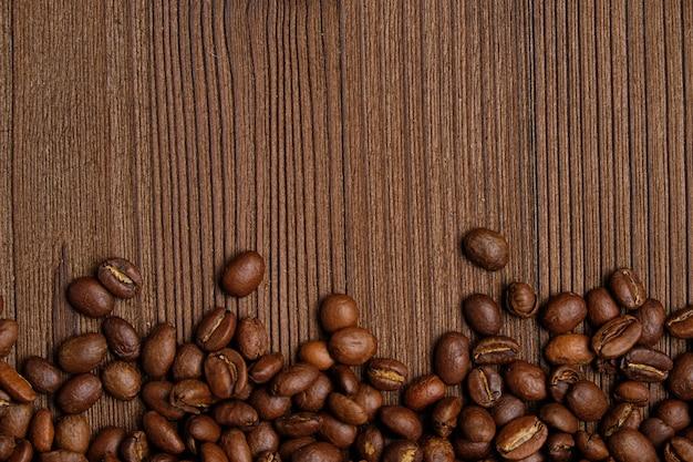 Geroosterde koffiebonen op een verkoolde houten plankachtergrond
