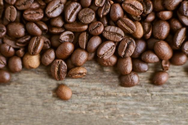 Geroosterde koffiebonen op rustieke houten achtergrond. voedselingrediënten, bovenaanzicht