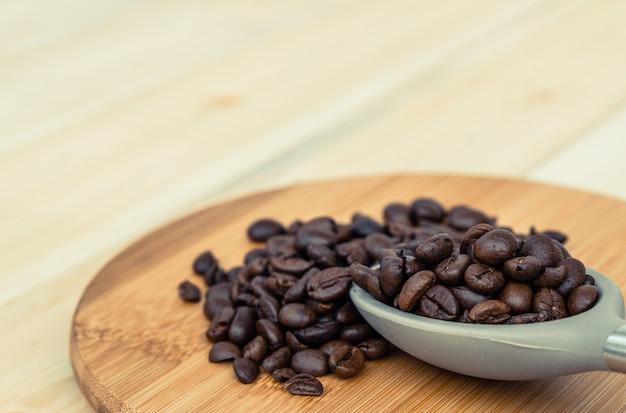 Geroosterde koffieboon in de lepel gezet op houten lijst