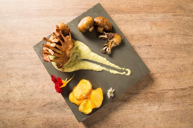 Geroosterde kwartel met rozemarijn en kruiden op de houten achtergrond.