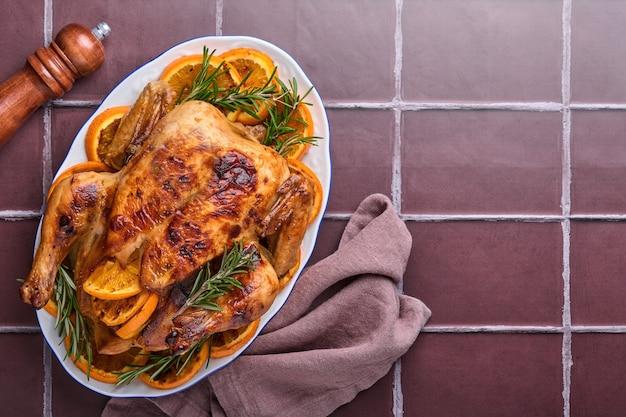 Geroosterde of gebakken hele kip met rozemarijn en sinaasappel, huisgemaakt voor een familiediner op een bruine stenen tafel. bovenaanzicht met kopie ruimte.