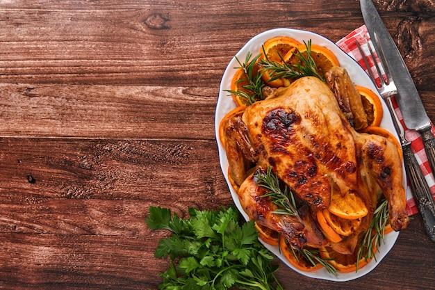 Geroosterde of gebakken hele kip met rozemarijn en sinaasappels, zelfgemaakt voor het traditionele familiediner van kerstmis op een oude houten rustieke tafel. bovenaanzicht met kopie ruimte.