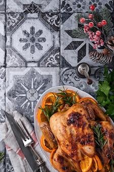 Geroosterde of gebakken hele kip met rozemarijn en sinaasappels, zelfgemaakt voor het traditionele familiediner van kerstmis op een oude steengrijze rustieke tafel. bovenaanzicht met kopie ruimte.