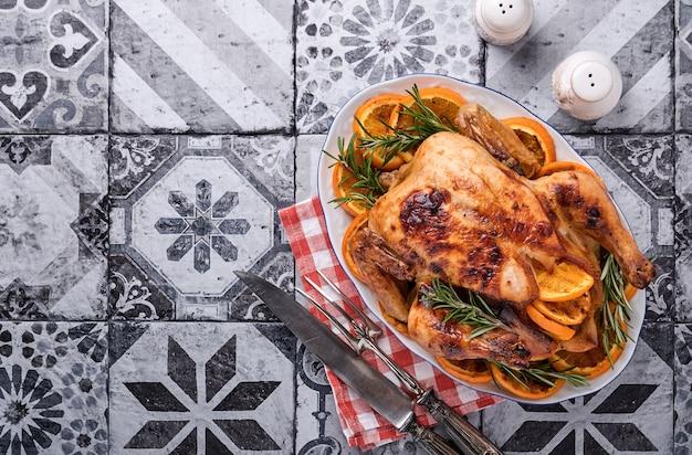 Geroosterde of gebakken hele kip met rozemarijn en sinaasappels, zelfgemaakte voor het traditionele familiediner van kerstmis op steengrijze rustieke tafel. bovenaanzicht met kopie ruimte.