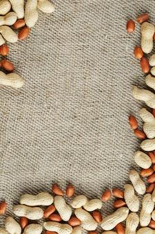 Geroosterde pinda's in een schaal en gepeld op een bruine stof.