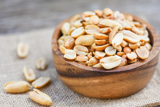 Geroosterde pinda's op een houten kom en zak - gezouten pinda's als voedsel of snack