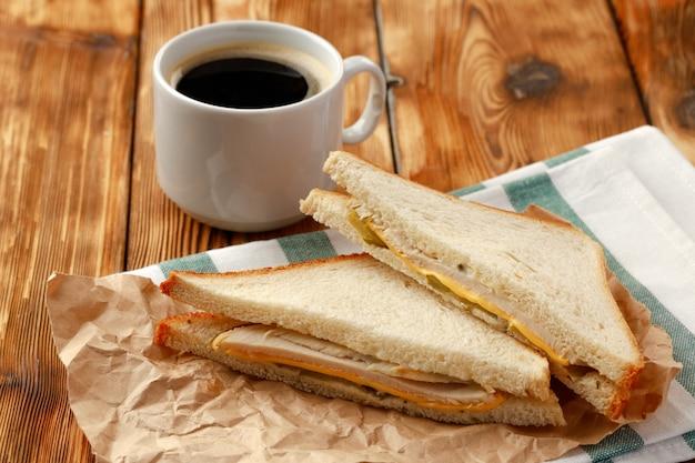 Geroosterde sandwich in ambachtelijk papier met een kopje koffie op tafel clsoe up