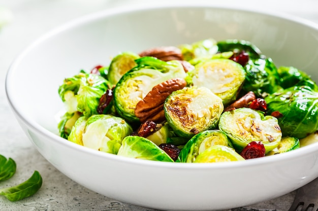 Geroosterde spruitjessalade met amerikaanse veenbessen en noten in witte kom