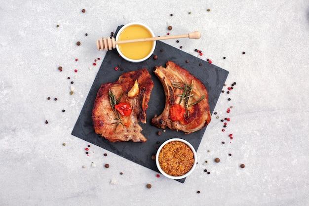 Geroosterde varkenslende steaks met kruiden op zwarte steen.