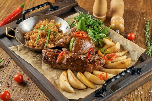 Geroosterde varkensschenkel eisbein in bier en honing met tomaat, kool en aardappel. traditioneel duitsland bier eten.