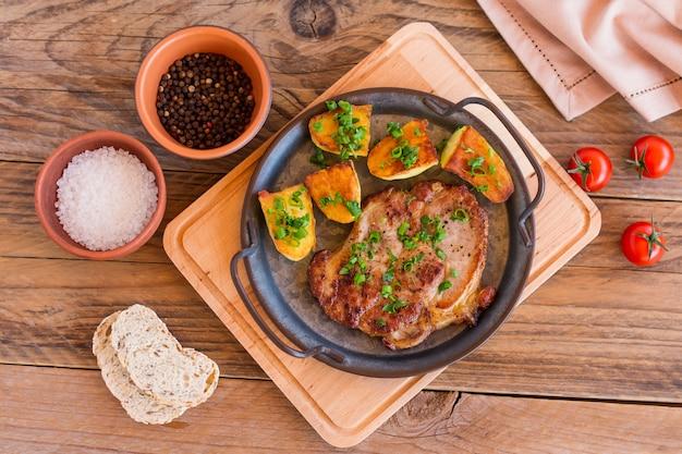 Geroosterde varkensvleeslapjes vlees in pan van halsvlees met aardappel. houten achtergrond.
