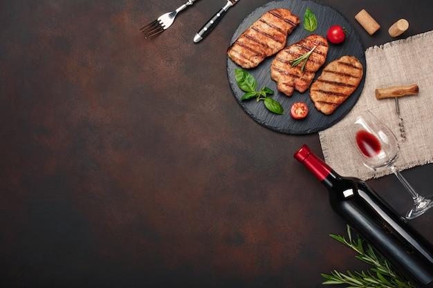 Geroosterde varkensvleeslapjes vlees op steen met fles wijn, wijnglas, mes en vork op roestige achtergrond