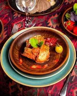 Geroosterde vis in tomatensaus geserveerd met granaatappelpitjes, cherrytomaat en plakjes peper