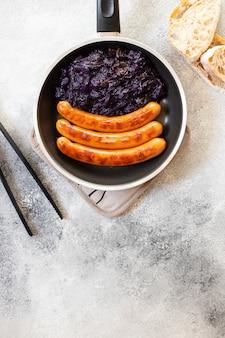 Geroosterde worst braadworst geserveerd in pan met brood en rode kool op een grijze achtergrond. traditioneel duits gerecht, duitse keuken. bovenaanzicht, kopieer ruimte