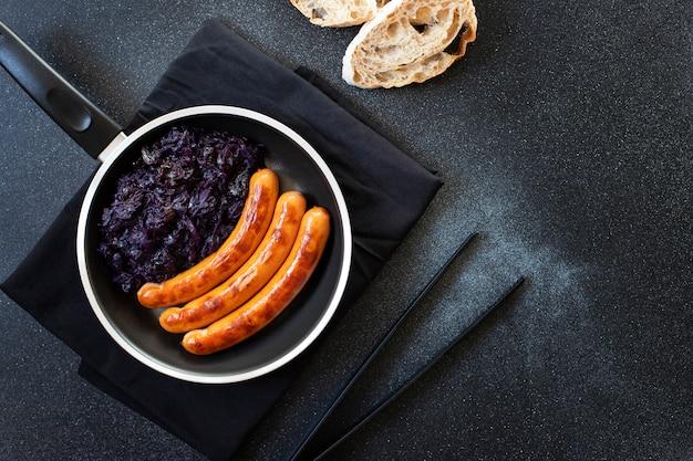 Geroosterde worst braadworst geserveerd in pan met brood en rode kool op een zwarte achtergrond. traditioneel duits gerecht, duitse keuken. bovenaanzicht, kopieer ruimte