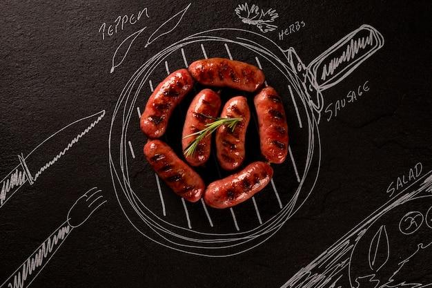 Geroosterde worst op zwart bord met geschilderde pan en ingrediënten. bovenaanzicht. barbecue concept.