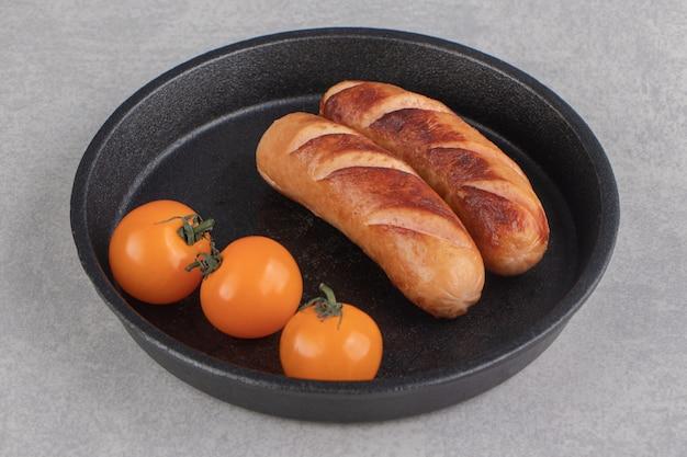 Geroosterde worstjes en tomaten op zwarte plaat.