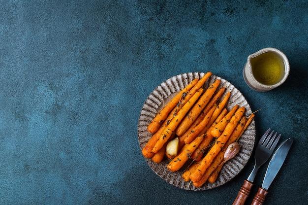 Geroosterde wortelen klaar om te eten. geglazuurde wortel met kruiden en knoflook bovenaanzicht. gebakken wortel op donkere achtergrond. gebakken groenten. troosteten. duurzame consumptie