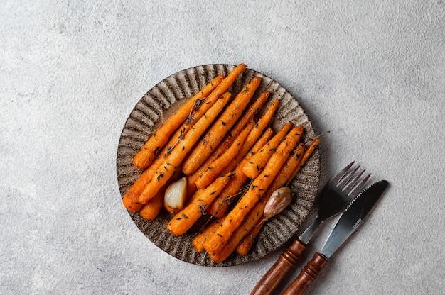 Geroosterde wortelen klaar om te eten. geglazuurde wortel met kruiden en knoflook. gebakken wortel op witte achtergrond. gebakken groenten. troosteten. kerst garnering