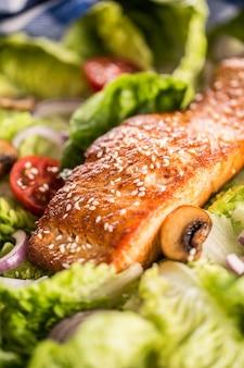 Geroosterde zalmfilet met verse groentesalade, tomaten, champignons en sesam.