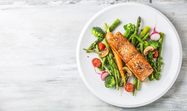 Geroosterde zalmsteak met asperges broccoli wortel tomaten radijs sperziebonen en doperwten