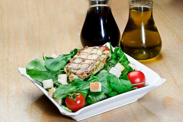 Geroosterde zwarte peper lamsbiefstuk met salades en frietjes op een blauwe ronde plaat. houten textuur achtergrond.