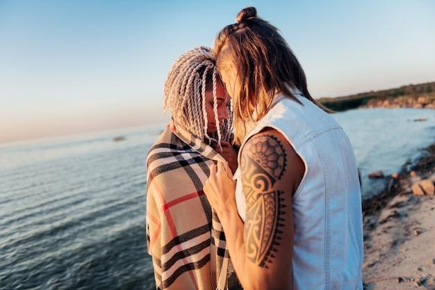 Geruit op schouders. liefdevolle zorgzame man plaid zetten schouders van zijn vriendin staande in de buurt van zee