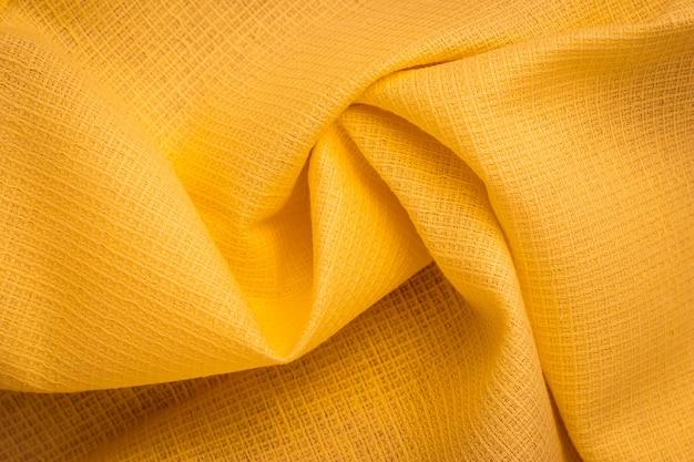 Geruit oppervlak van tricot. vouwen van natuurlijk gegolfd tricot, geel textiel. stoffenpatroon, materiaal.