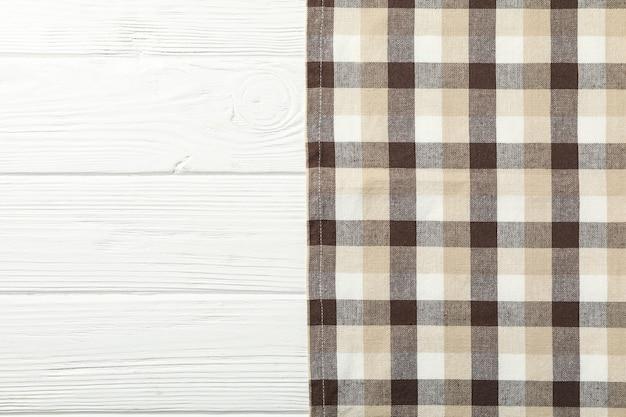 Geruit tafelkleed op witte houten tafel, ruimte voor tekst