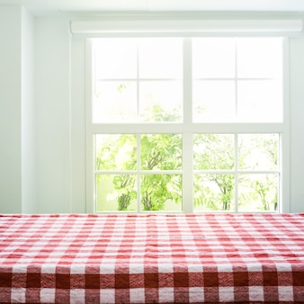 Geruit tafelkleed textuur bovenaanzicht op onscherpte venster weergave tuin achtergrond.