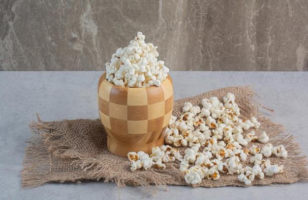 Geruite kom vol popcorn op een stuk doek met een handvol popcorn op marmeren oppervlak