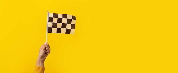 Geruite vlag ter beschikking over gele achtergrond, panoramisch beeld