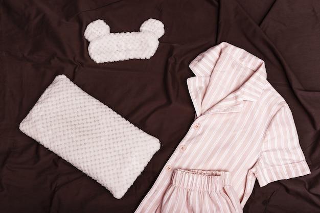Geruite warme pyjama's voor dames, zacht kussen en oogmasker voor het slapen op een donkere deken op bed.