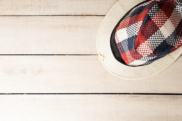 Geruite zomerhoed op een witte houten tafel, bovenaanzicht