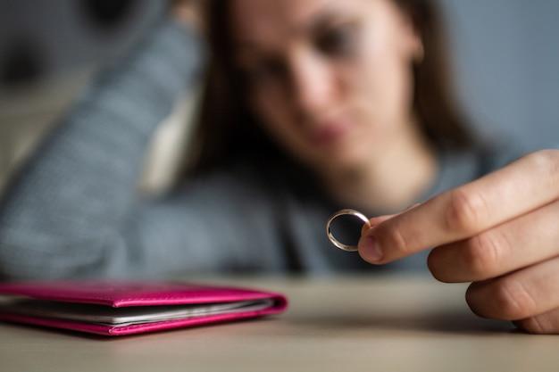Gescheiden vrouw houdt een trouwring in haar handen en huilt