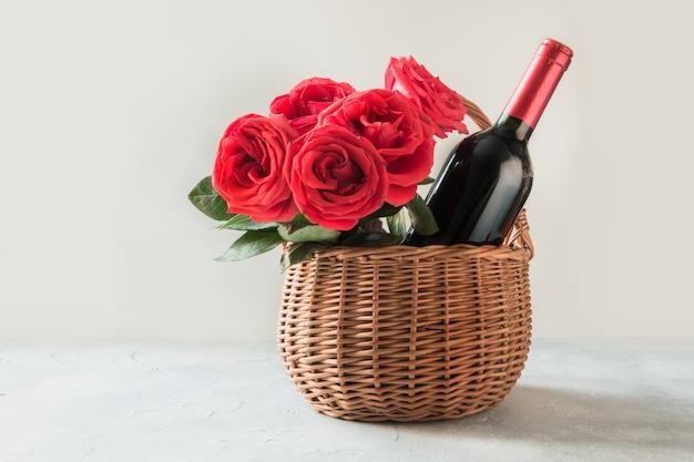 Geschenk belemmert, boeket rode rozen, fles rode wijn op wit.