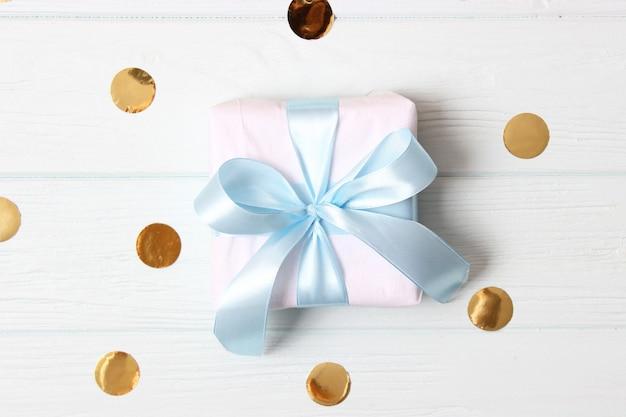 Geschenk en glitters van confetti op een gekleurde achtergrond bovenaanzicht minimalisme