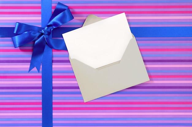 Geschenk gemaakt van gestreept papier met blauw satijnen lint en blanco berichtkaart.