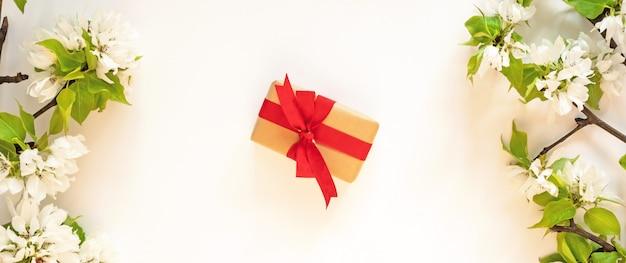 Geschenk huidige doos, appelboom bloesem tak, witte muur plat lag. de bloemenlente bloeit het rode concept van de giftdoos