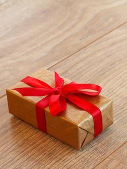Geschenk of huidige doos verpakt in kraftpapier met rood lint op houten planken. bovenaanzicht met kopie ruimte.