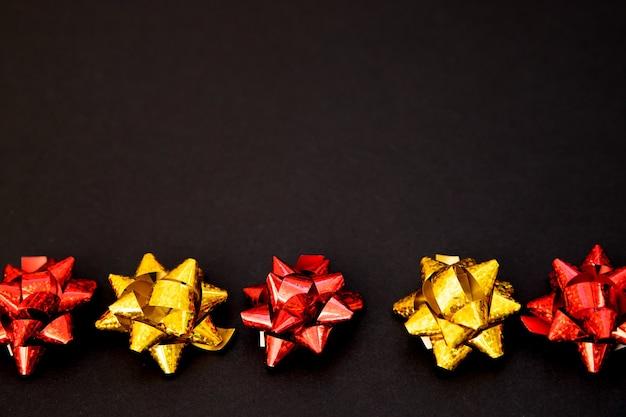 Geschenk strikken liggen in een lijn op een zwarte achtergrond. kerstmis en nieuwjaar. een verjaardagscadeau. lege ruimte voor de tekst. stijlvolle vakantie achtergrond.
